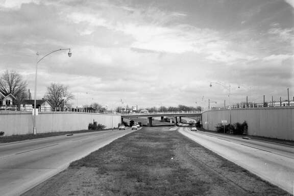The San Antonio Expressway is shown in this circa 1950s photo. It is on I-10 northwest of downtown. The overpass is Woodlawn Avenue, and just beyond that is Fredericksburg Road. This photo was taken sometime in the 1950s when the roadway was US 87. The freeway ended there at Fredericksburg Road, and in the background, you can see where it curves to the left to merge onto Fredericksburg. This was the first section of freeway in San Antonio.