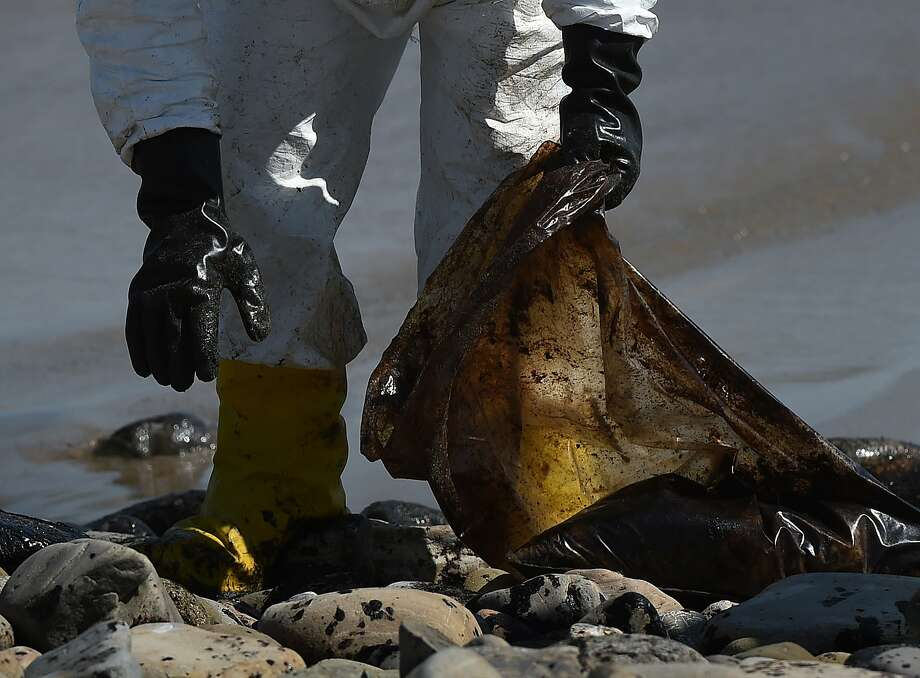 """A worker cleans oil from the rocks and beach at Refugio State Beach in Goleta (Santa Barbara County) on May 22. The oil company behind a crude spill on the California coast vowed to do the """"right thing"""" to clear up the mess, even as reports emerged of past leaks involving its pipelines. Plains All American Pipeline made the pledge as it said nearly 8,000 gallons of oil had been scooped up, out of some 21,000 gallons believed to have flooded into the ocean near Santa Barbara, northwest of Los Angeles. Photo: Mark Ralston, AFP / Getty Images"""