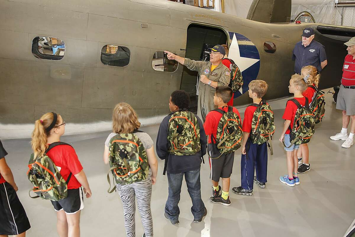 Frank Vargas who is a pilot for Wings over Houston, talks with students from Katy Elementary about WWII planes and jumping out of a plane with a parachute at the Commemorative Air Force's Hanger located at West Houston Airport on May 22, 2015.