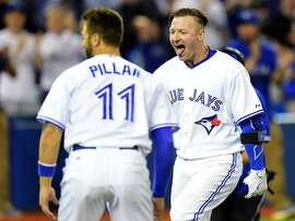 Toronto Blue Jays' Josh Donaldson celebrates with teammate Kevin Pillar after hitting a three run game winning homer against the Chicago White Sox picher David Robertson during ninth inning American League baseball action in Toronto on Tuesday, May 26, 2015. (Frank Gunn/The Canadian Press via AP) MANDATORY CREDIT