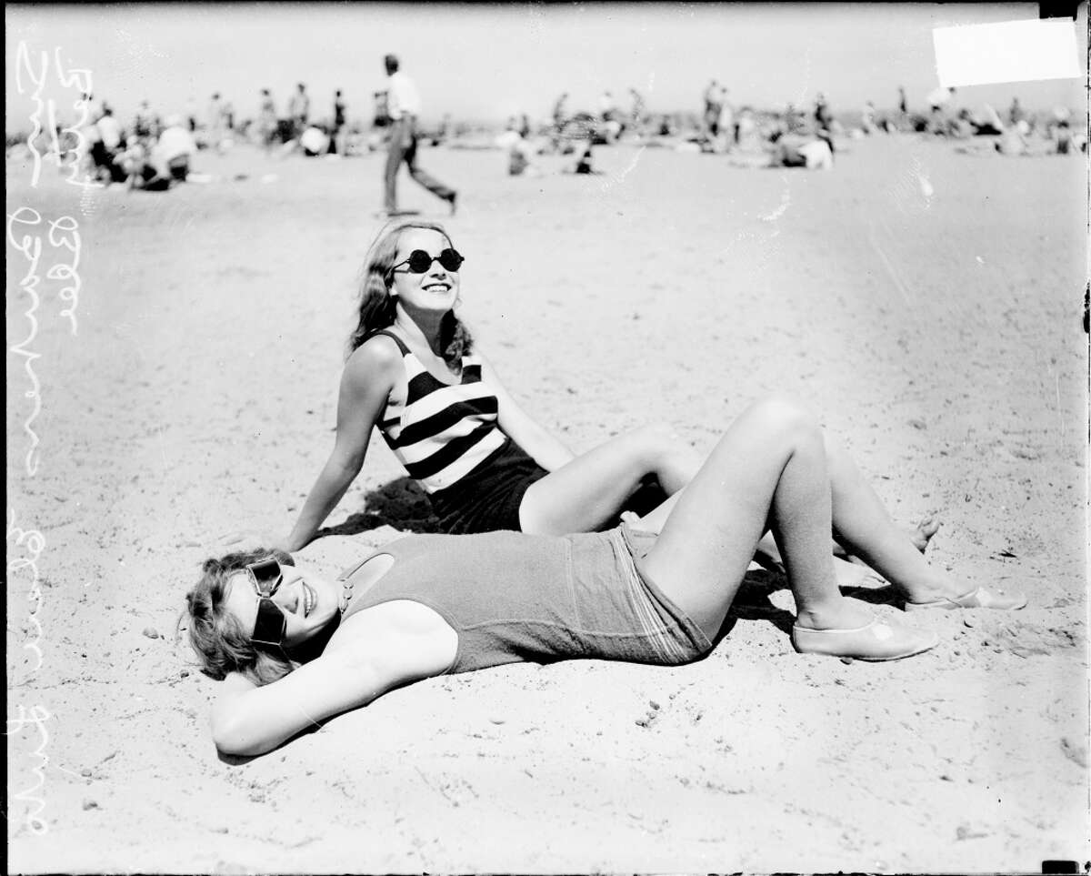 Informal full-length portrait of Elsie Luto and Betty Blee wearing bathing suits and sunglasses, posing on the sand at Wilson Avenue bathing beach in the Uptown community area of Chicago, Illinois, 1929.