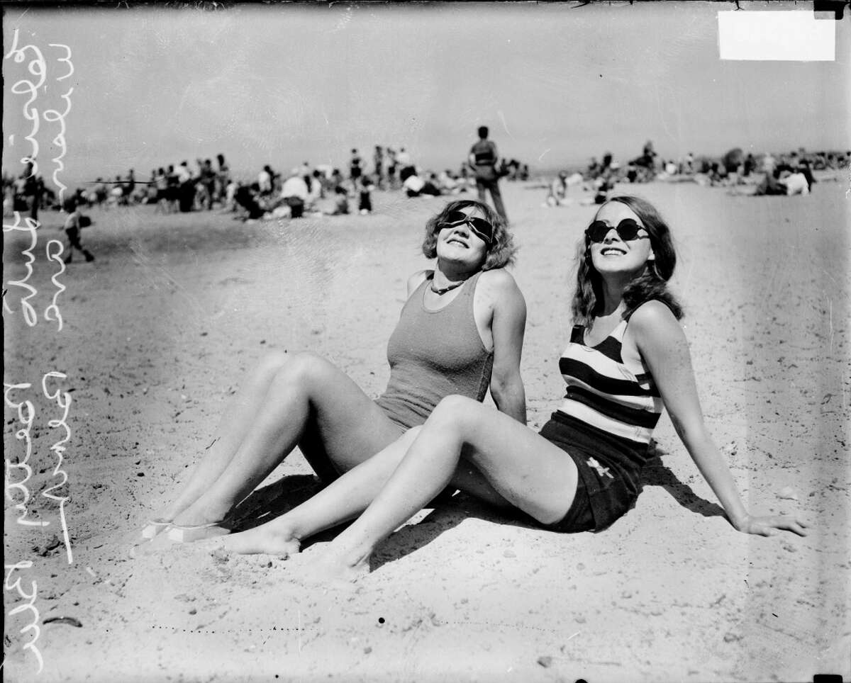 Informal full-length portrait of Elsie Luto and Betty Blee wearing bathing suits and sunglasses and looking up, sitting on the sand at Wilson Avenue bathing beach in the Uptown community area of Chicago, Illinois, 1929.
