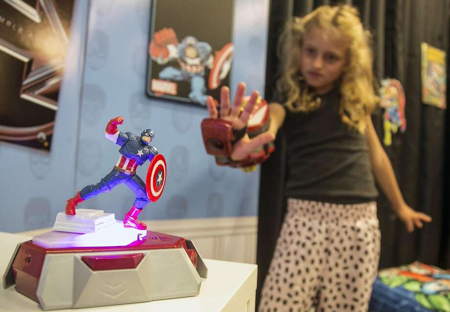 "In this Friday, May 29, 2015 photo, actress Evangeline Lindes role demonstrates a Playmation ""repulsor"" a wearable forearm attachment that puts kids in the role of Marvel superhero Iron Man, that connects via sensors with a base station called a ""power activator,"" at left, at the Disney Consumer Products offices in Glendale, Calif. Disney is launching its new Playmation line of toys that combine high-tech wearable gadgets and old-school superhero role-playing to keep kids moving while engrossing them in sub-plots from ""The Avengers,"" ""Star Wars"" and ""Frozen."" (AP Photo/Damian Dovarganes) Photo: Damian Dovarganes, Associated Press"
