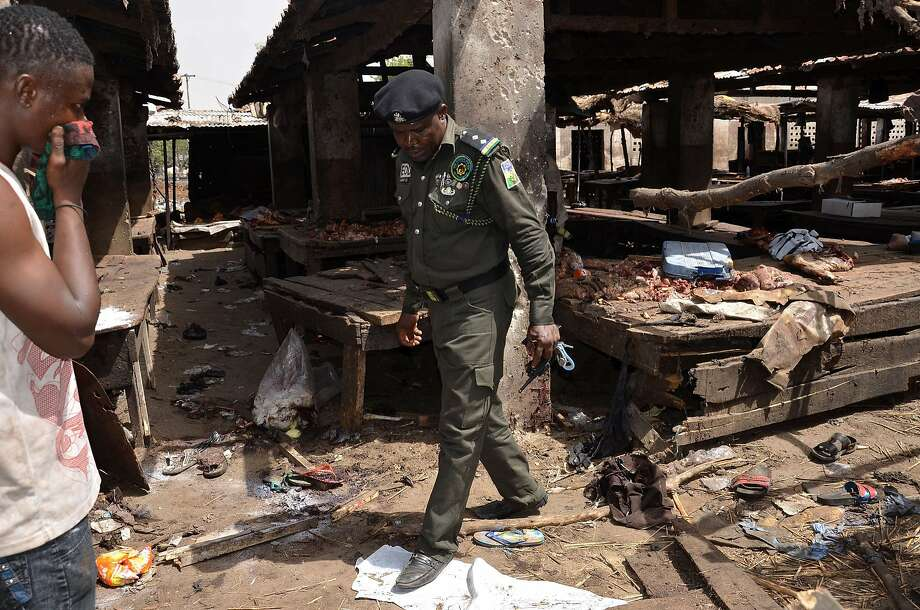 A Nigerian policeman inspects the site of a suicide attack at a busy cattle market in the northeastern Nigerian city of Maiduguri. Photo: Stringer, AFP / Getty Images