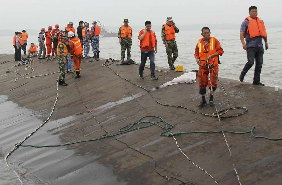 Rescue workers walk on the hull of a capsized cruise ship on the Yangtze River in Jianli in central China's Hubei province Tuesday, June 2, 2015. Divers on Tuesday pulled survivors from inside the overturned cruise ship, state media said, giving some small hope to an apparently massive tragedy with well over 400 people still missing on the river. (Chinatopix Via AP) CHINA OUT Photo: Associated Press