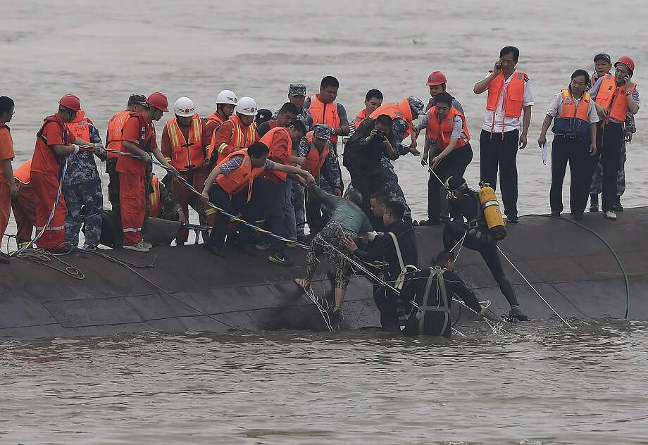 In this photo released by China's Xinhua News Agency, rescuers save a survivor, center, from the overturned passenger ship in the Jianli section of the Yangtze River in central China's Hubei Province Tuesday, June 2, 2015. Rescuers pulled several survivors to safety after hearing cries for help Tuesday from inside a capsized cruise ship that went down overnight in a storm on China's Yangtze River, state broadcaster CCTV said. (Cheng Min/Xinhua via AP) NO SALES Photo: Cheng Min, Associated Press