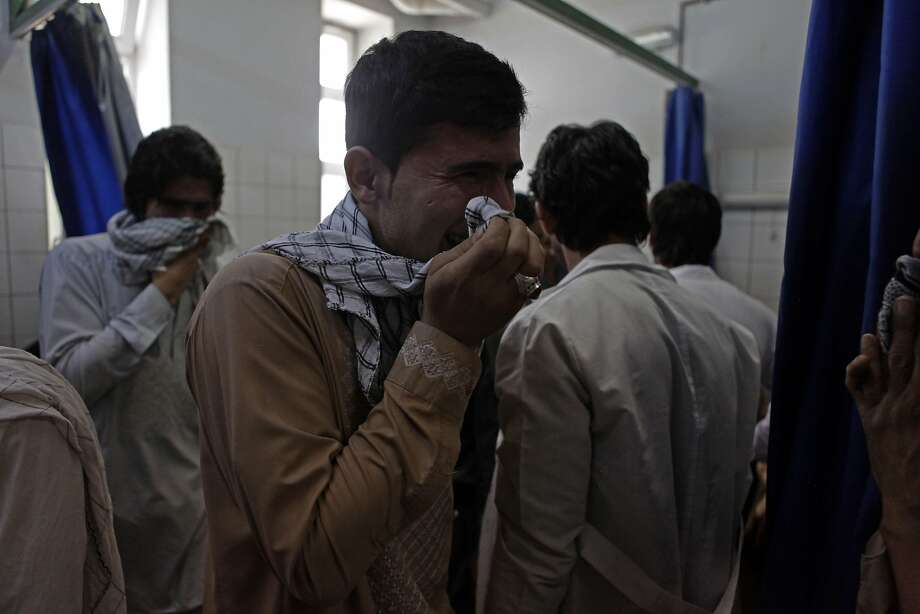An Afghan relative cries after seeing the body of his brother a slain aid worker, at a hospital of Mazar-i-Sharif. Photo: Bashir Dawodi, AFP / Getty Images