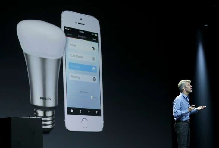 """FILE - In this June 2, 2014 file photo, Apple senior vice president of Software Engineering Craig Federighi speaks about the Apple HomeKit app at the Apple Worldwide Developers Conference in San Francisco. The first """"smart"""" home gadgets that can be controlled by Apple's voice-activated digital assistant are going on sale this week, just days after rival tech giant Google announced its own software for Internet-connected home appliances and other gadgets. (AP Photo/Jeff Chiu, File)"""