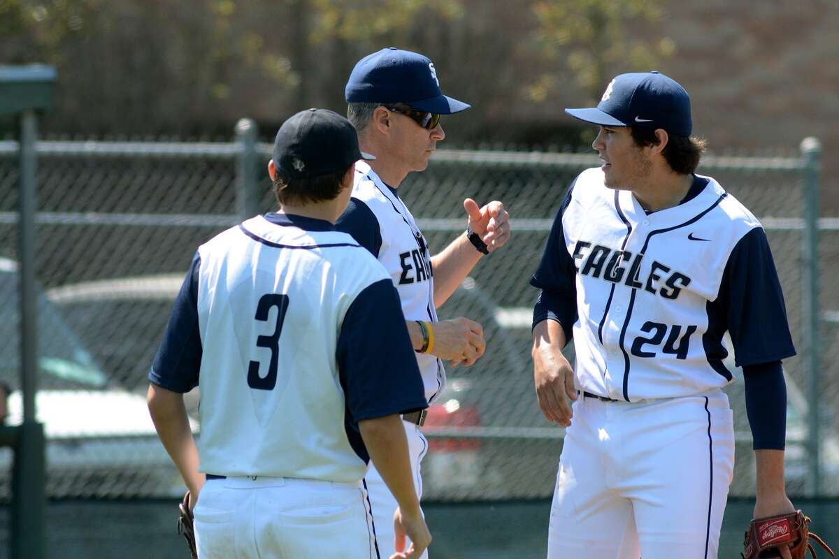 Second Baptist Head Coach Jeff Schroeder, center, makes a pitching change from sophomore Davis Fielding (24) to junior Grayson Skweres (3) during their game against Cypress Christian at Second Baptist School on March 14.