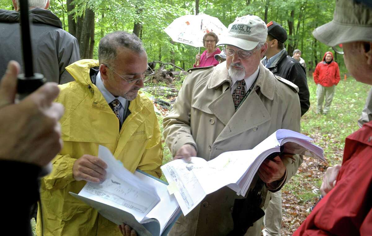 Carlo Centore, from Centek Engineering Inc.,right, goes over his notes on the site of a proposed new cell tower with Bob Hannon, the DEEP Commissioner Designee to the Connecticut Siting Council. Siting Council officials and members of the public took a tour of the site for the proposed new cell tower, on Tuesday, June 2, 2015, in Bethel, Conn. Centek is the firm that did the site design for the proposed telecommunications tower.