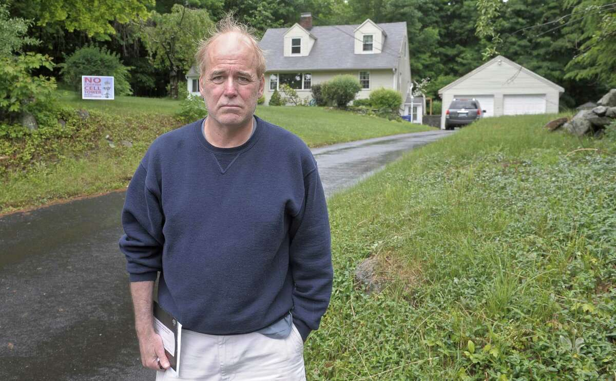 Arthur Gow, of Bethel, stands at the end of his driveway on Codfish Hill Road as Connecticut Siting Council officials and members of the public head to the site of a proposed new cell tower 2 doors down from his property, in Bethel, Conn, on Tuesday, June 2, 2015.