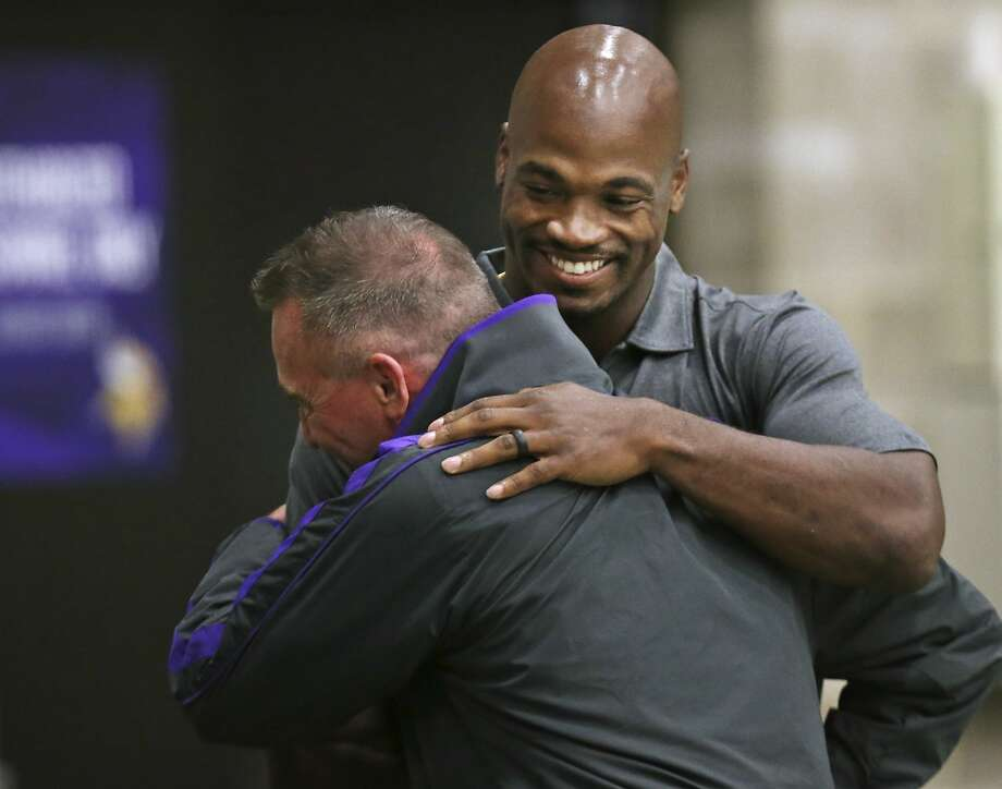 Running back Adrian Peterson (rear) hugs Vikings public relations director Brad Madson before a news conference marking his return to the team from a long suspension. Photo: Jerry Holt, Associated Press