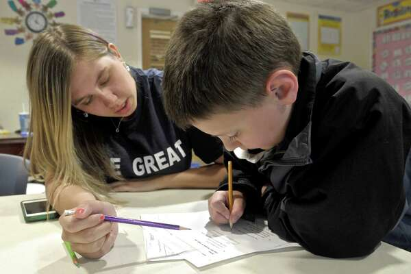Grant Terbrusch, 7, gets some help with his homework from Alyssa Alt, of Ridgefield, in the study room at the Ridgefield Boys & Girls Club, on June 2, 2015, in Ridgefield, Conn. The Boys & Girls Club was named the Best Overall Program in the country at the Boys & Girls Club of America's 109th national conference. Alt is a student at Merrimack College home for the summer and working at the club.