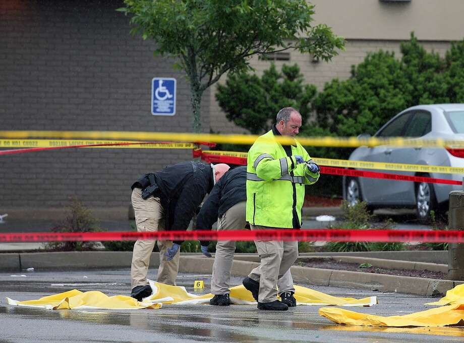 Boston police officers and detectives investigate at the scene of a shooting Tuesday morning, June 2, 2015) at 4600 Washington St. in Roslindale, Mass. A man under surveillance by terrorism investigators has been shot and killed by a Boston police officer. Police Commissioner William Evans confirmed from the scene that the man shot at about 7 a.m. at a pharmacy in the city's Roslindale neighborhood has died. Evans said the man was under surveillance by the Joint Terrorism task Force.  (Mark Garfinkel/The Boston Herald via AP)  BOSTON GLOBE OUT; METRO BOSTON OUT; MAGS OUT; ONLINE OUT Photo: Mark Garfinkel, Associated Press