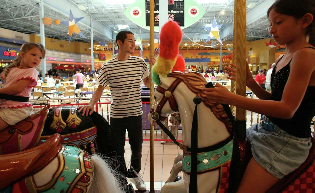 Children ride the carousel in the food court at Katy Mills Mall.
