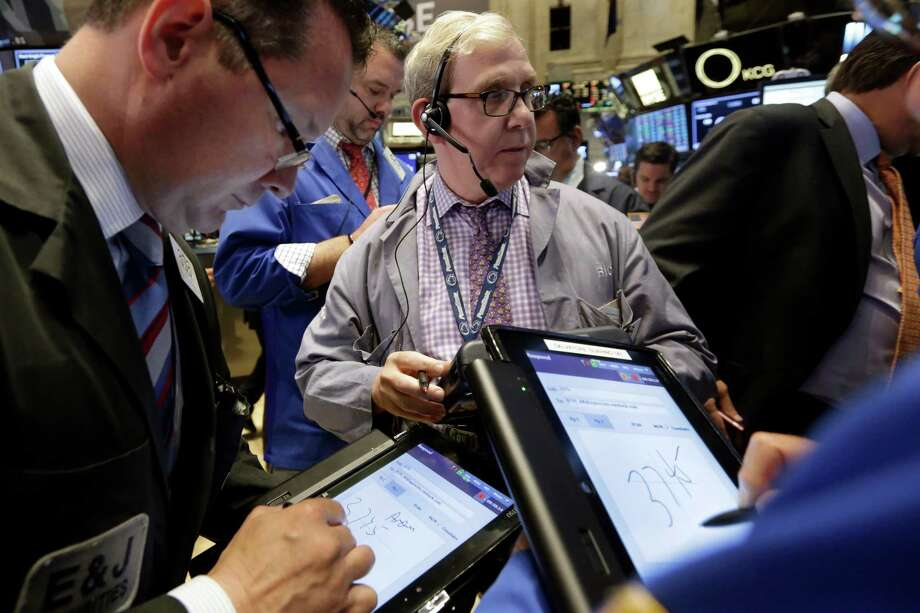 Trader Richard Cohen, center, works on the floor of the New York Stock Exchange, Tuesday, June 2, 2015. U.S. stocks are opening lower as investors fret over Greece's shaky finances. (AP Photo/Richard Drew) ORG XMIT: NYRD106 Photo: Richard Drew / AP