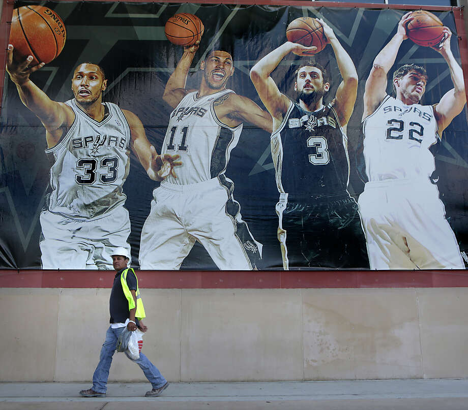 A construction worker walks past a banner showing Spurs players on Tuesday June 2, 2015, at the ATT Center where major interior redesign is taking place. Photo: Bob Owen, Staff / San Antonio Express-News / ©2015 San Antonio Express-News