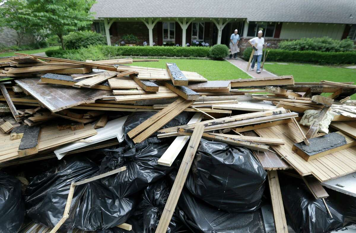 Workers remove materials from a home on Loch Lomond Dr. near North Braeswood Blvd. on Tuesday that were damaged in last week's. City and federal officials will answer questions at meetings set for Wednesday.