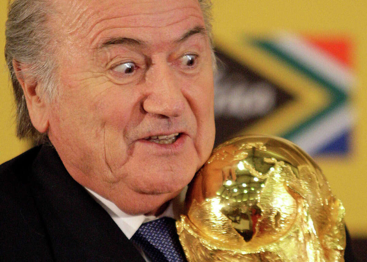 In this Sunday June 6, 2010 file photo FIFA President Joseph Blatter holds the trophy after receiving it back from South African President Jacob Zuma during a media briefing on the 2010 Soccer World Cup in Pretoria, South Africa.