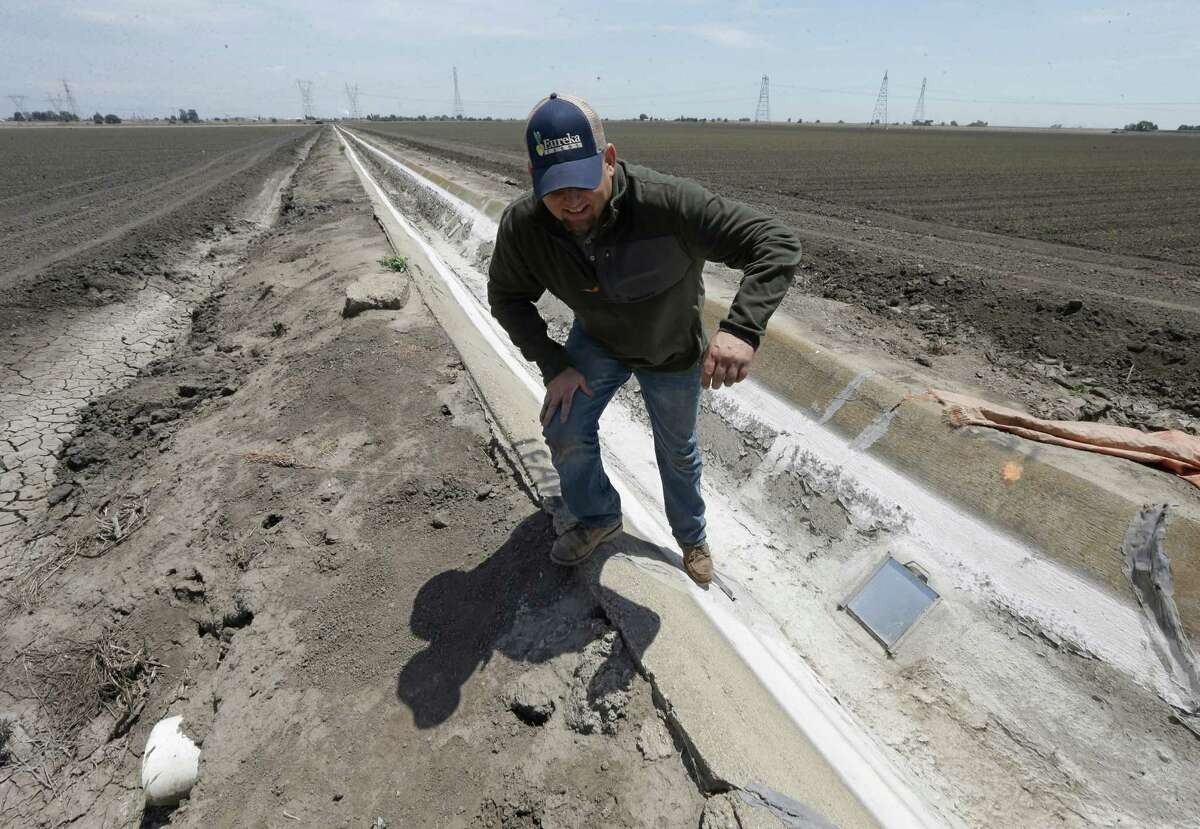 FILE - Ihis Monday, May 18, 2015, file photo, farmer Gino Celli climbs out of a irrigation canal that is covered in dried salt on a field he farms near Stockton, Calif. Moving to meet voluntary water conservation targets, dozens of farmers in the Sacramento-San Joaquin River Delta submitted plans Monday, June 1 to the state saying they intend to plant less thirsty crops and leave some fields unplanted amid the relentless California drought, officials said. (AP Photo/Rich Pedroncelli,File) ORG XMIT: LA102