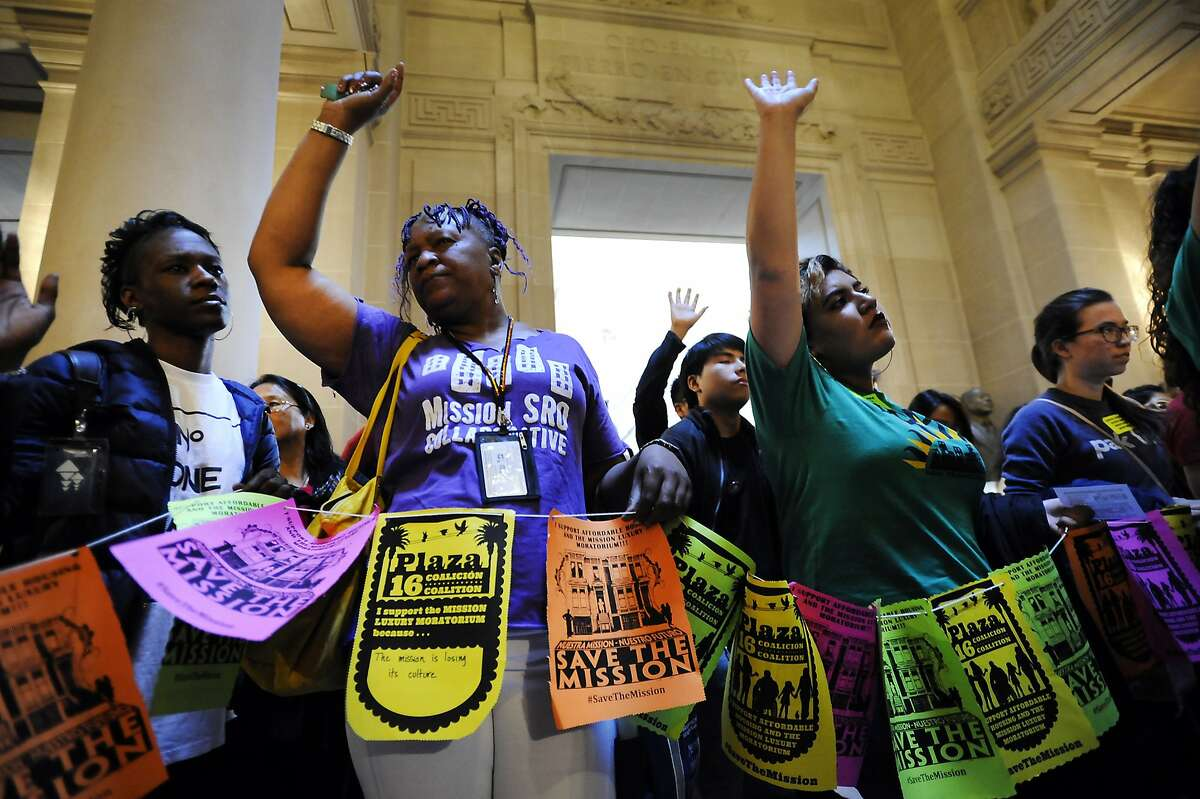Activists and protestors raise their hands as they hold a prayer circle in front of the mayors office as a board of supervisors meeting takes place where supervisor David Campos was expected to introduced a bill placing a temporary moratorium on the construction of new market-rate residential developments, at City Hall in San Francisco, CA Tuesday, June 2, 2015.