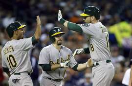 Oakland Athletics' Ben Zobrist, right, is greeted by teammates Marcus Semien (10) and Billy Burns after they scored on the grand slam by Zobrist off Detroit Tigers relief pitcher Angel Nesbitt during the seventh inning of a baseball game, Tuesday, June 2, 2015, in Detroit. (AP Photo/Carlos Osorio)