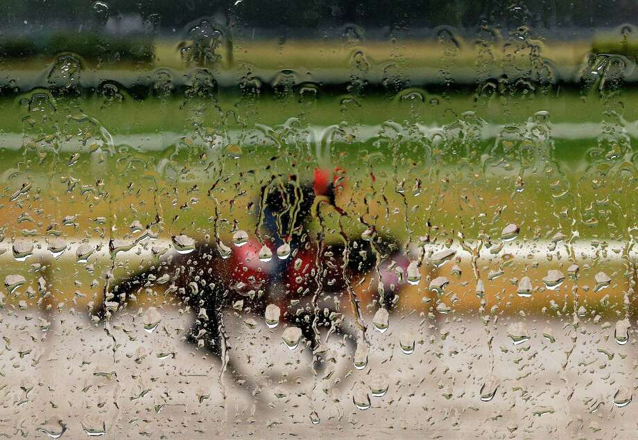 Rainwater coats the window of an observation tower as an exercise rider guides a horse around the main track at Belmont Park, Tuesday, June 2, 2015, in Elmont, N.Y. Kentucky Derby and Preakness Stakes winner American Pharoah will try for a Triple Crown Saturday, June 6, in the Belmont Stakes horse race  Photo: Julie Jacobson, Associated Press / AP