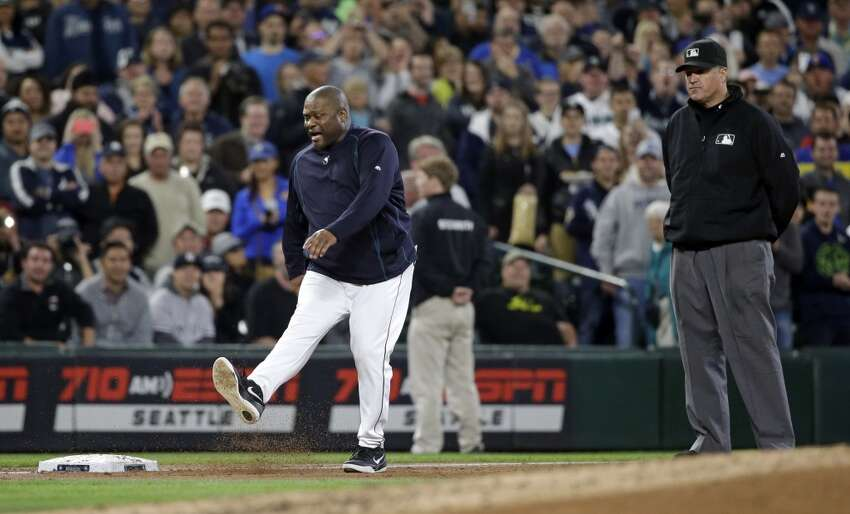 Umpire Tony Randazzo, right, looks on as Seattle Mariners manager Lloyd McClendon kicks along the third baseline after being ejected in the third inning of a baseball game Tuesday, June 2, 2015, in Seattle. (AP Photo/Elaine Thompson)