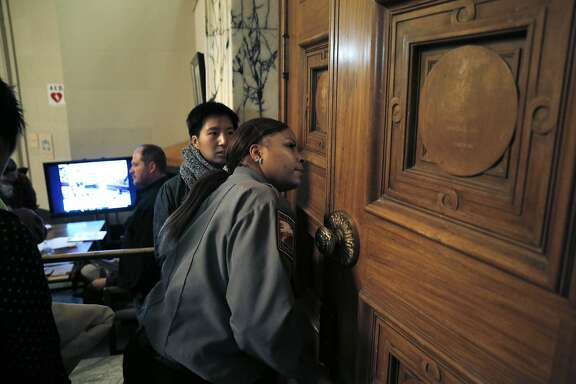 A private security guard peeks through the door to see if there is room to allow a speaker into the council chambers on Tuesday. Housing advocates rallied outside Oakland City Hall before trying to enter the council chambers in Oakland, Calif., on Tuesday, June 2, 2015. A takeover of the council chambers a month ago prompted a measured capacity to the room with auxiliary viewing rooms available for overflow attendance.