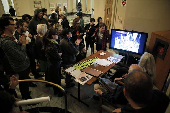 Housing advocates watch the city council meeting on a TV outside the chambers after they rallied outside Oakland City Hall before trying to enter the council chambers in Oakland, Calif., on Tuesday, June 2, 2015. A takeover of the council chambers a month ago prompted a measured capacity to the room with auxiliary viewing rooms available for overflow attendance.