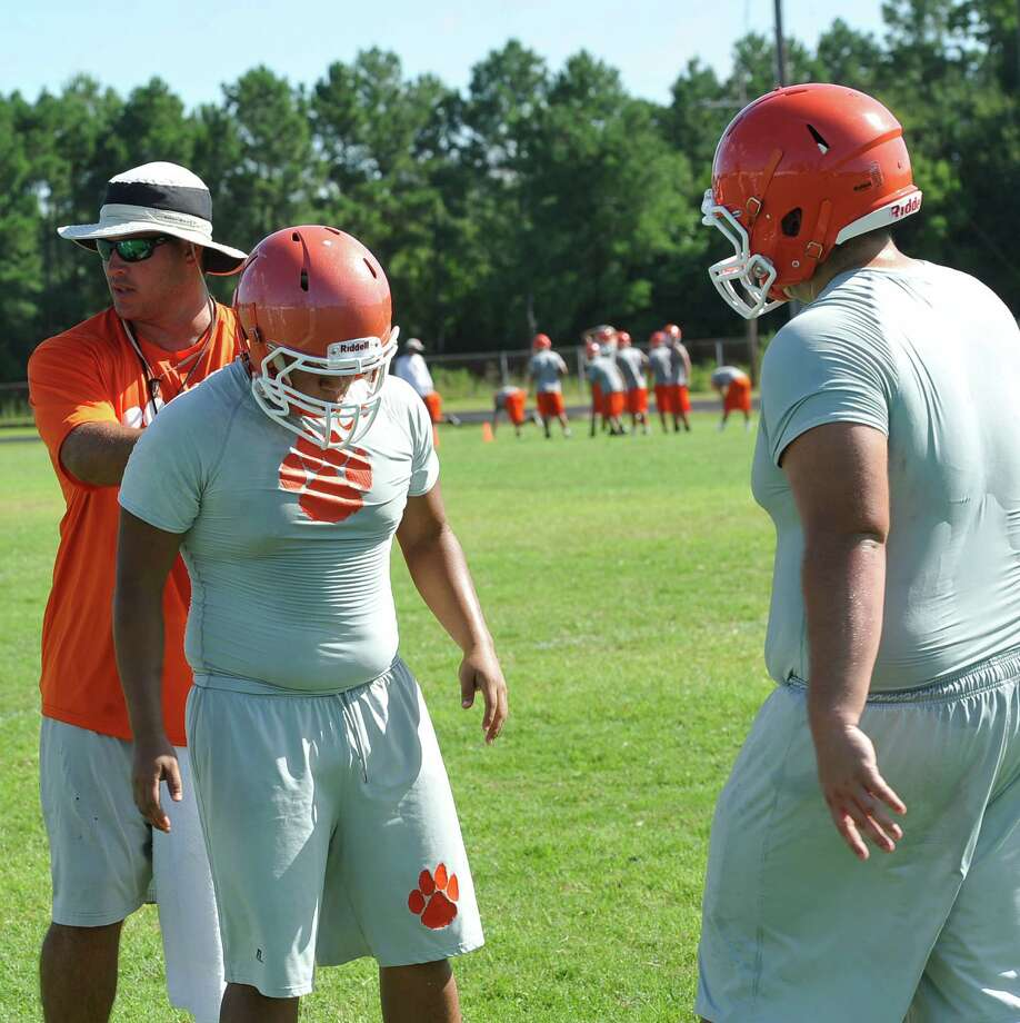 Defensive line coach Jared Gary, left, demonstrates where their eyes and hands should be on a player they are trying to block. The Orangefield High School football team held practice Tuesday from nine in the morning till noon.   Dave Ryan/The Enterprise Photo: Dave Ryan