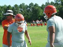Defensive line coach Jared Gary, left, demonstrates where their eyes and hands should be on a player they are trying to block. The Orangefield High School football team held practice Tuesday from nine in the morning till noon.   Dave Ryan/The Enterprise