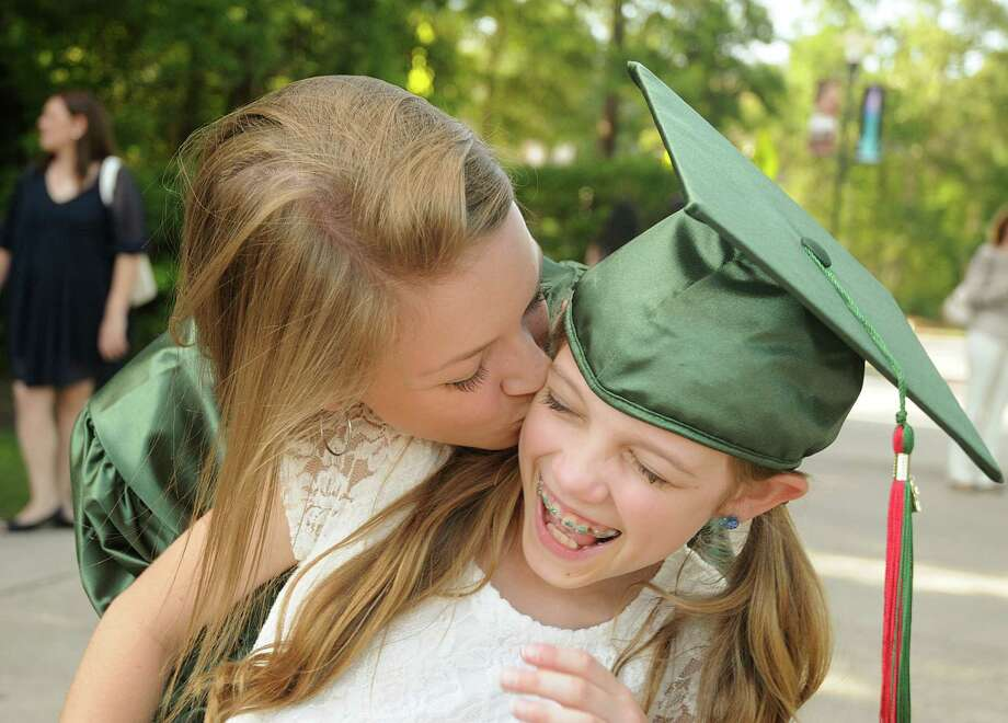 Graduate Chaise Armstrong goves her little sister, Salem, a surprise kiss during The Woodlands High School graduation ceremony at the Cynthia Woods Mitchell Pavilion. Photograph by David Hopper. Photo: David Hopper, For The Chronicle / freelance