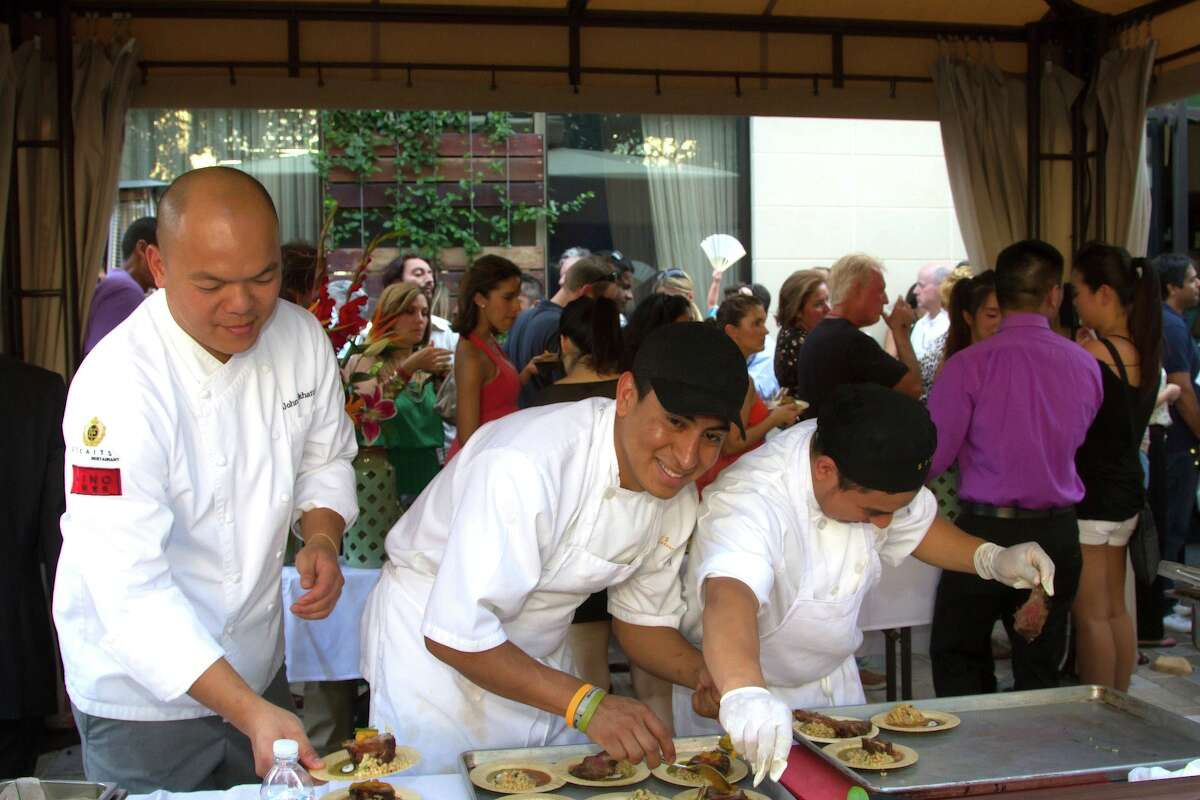 Chef John Sikhattana, left, of Straits, prepares dishes for guests at last year's Curry Crawl Chef Showdown.