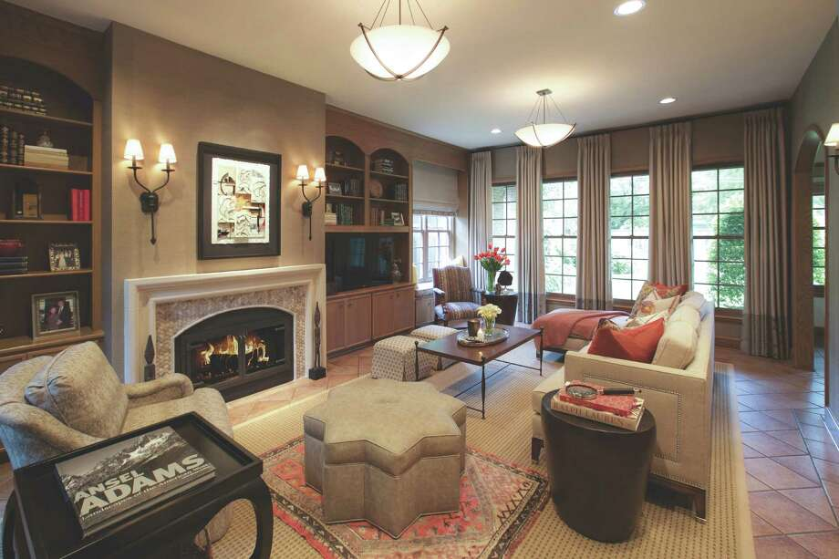 Designer Ben Johnston improved the room's proportions by adding a limestone mantel to the fireplace and hanging floor-to-ceiling drapes. Photo: Ben Johnston