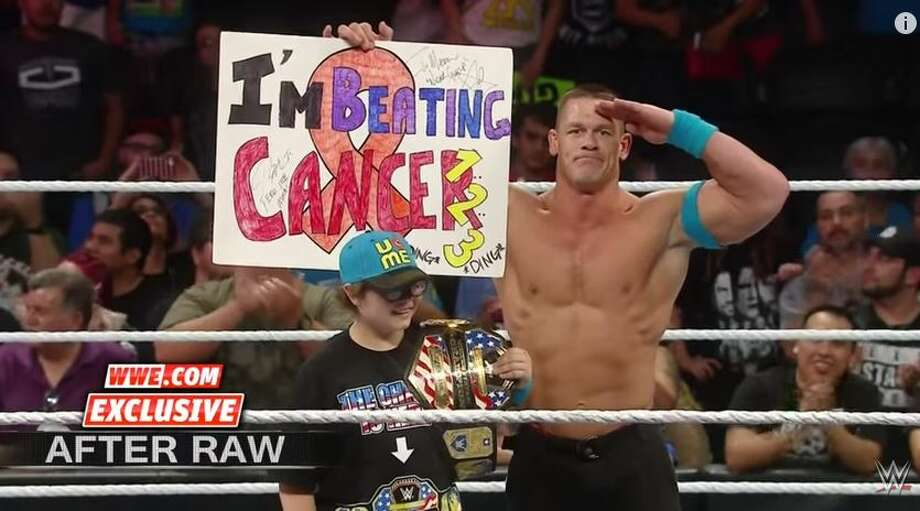 "Cena was in the middle of a showdown against wrestling foe Kevin Owens when he spotted the unidentified child standing near the ring, proudly holding a sign saying ""I'm beating cancer."" Photo: Mendoza,  Madalyn S, WWE,  YouTube.com"