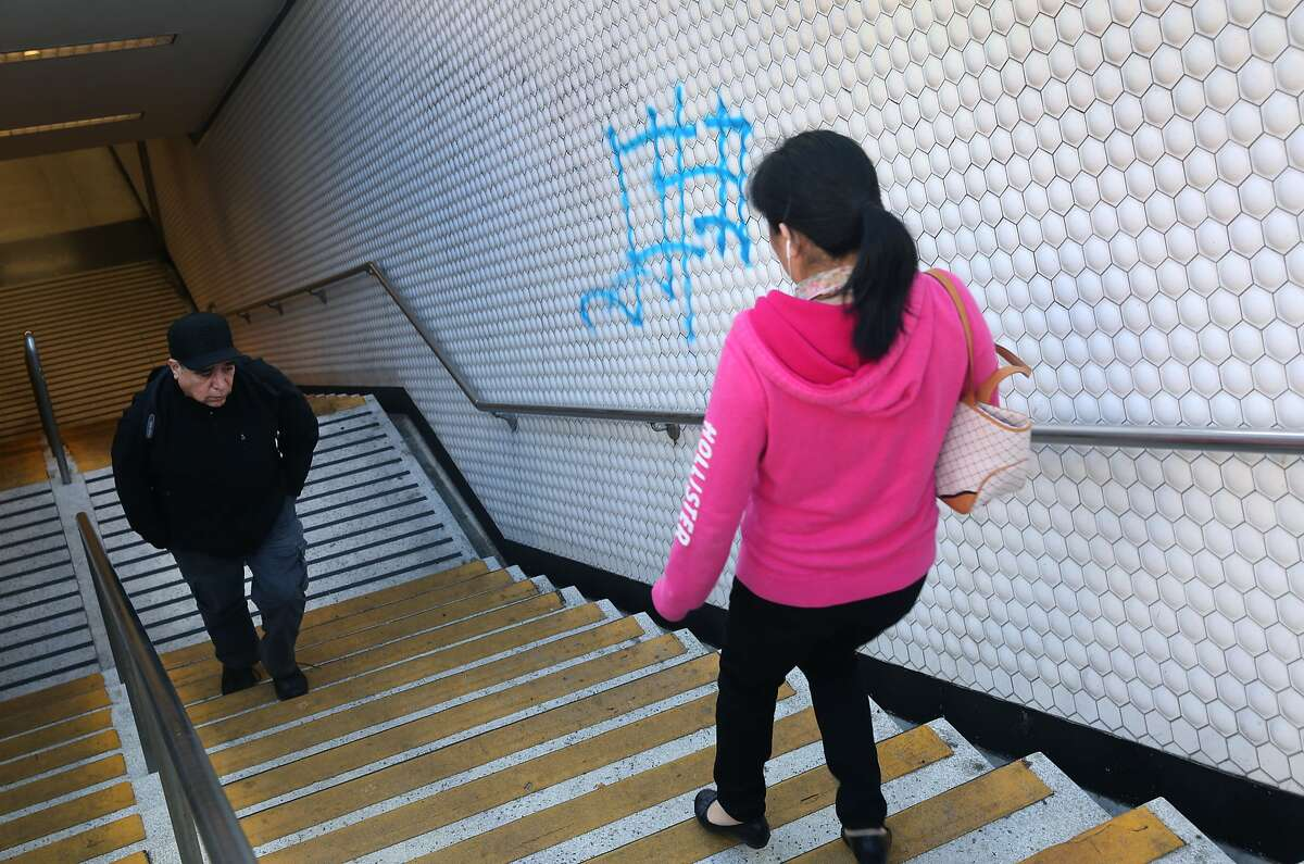 Commuters walk past graffiti sprayed on a stairwell at the Powell Street BART station in San Francisco, Calif. on Wednesday, June 3, 2015.