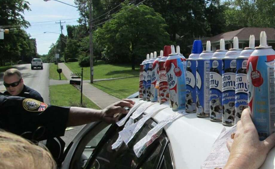 Police stack 13 canisters of whipped cream found in the SUV of a driver accused of DUI in Franklin, Tenn. Photo: Courtesy Franklin (Tenn) Police Dept.