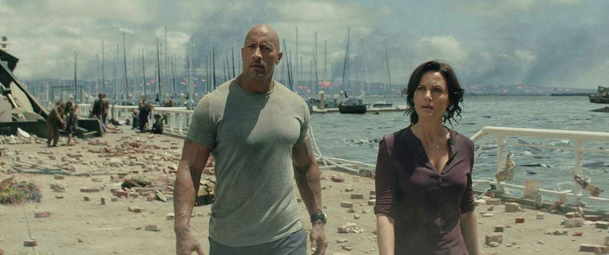 This photo provided by Warner Bros. Pictures shows Dwayne Johnson, left, as Ray, and Carla Gugino as Emma, in a scene from the action thriller,