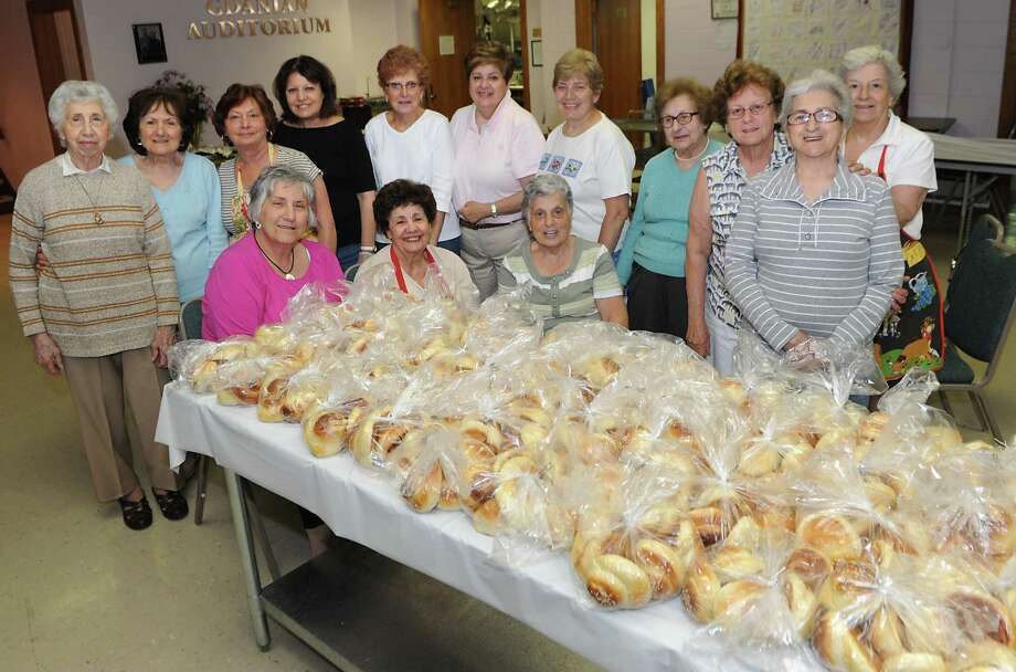 Women stand behind a table full of of choereg, an Armenian sweet bread, after baking and bagging it up at St. Peter Armenian Apostolic Church on Wednesday, June 3, 2015 in Watervliet, N.Y. The church is getting ready for its annual Armenian Festival this weekend. (Lori Van Buren / Times Union) Photo: Lori Van Buren / 00032133A