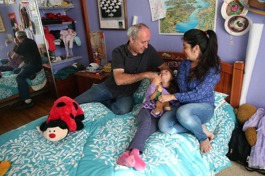 Dale Duncan and his wife Marta Munoz play with their 6-year-old daughter Emilia at their Mission District apartment in San Francisco, Calif. on Wednesday, June 3, 2015. Duncan, who's lived in the same unit for 21 years, is battling eviction by a controversial landlord that purchased the building last year. Photo: Paul Chinn, The Chronicle