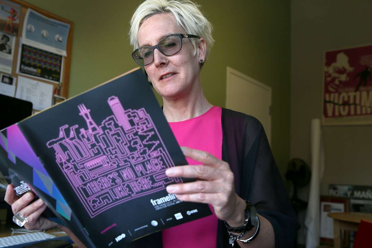 Frances Wallace, the new executive director of the Frameline film festival, flips through a program for this year's event in San Francisco, Calif. on Wednesday, June 3, 2015. The Frameline39 LGBTQ film festival opens June 18 and concludes June 28.