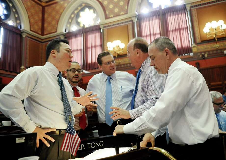 Connecticut State Rep. William Tong, D-Stamford, left, speaks with House Majority Leader Joseph Aresimowicz, D-Berlin, right, at the Capitol on the final day of session, Wednesday, June 3, 2015, in Hartford, Conn. Photo: Jessica Hill, AP Photo/Jessica Hill / Associated Press