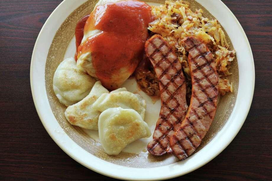 A view of a plate of potato and cheese pierogis, golobki (stuffed cabbage), grilling Polish kielbasa and bigos (sauerkraut stew) at Euro Deli on Thursday, May 28, 2015, in Latham, N.Y.     (Paul Buckowski / Times Union) Photo: PAUL BUCKOWSKI / 10032062A