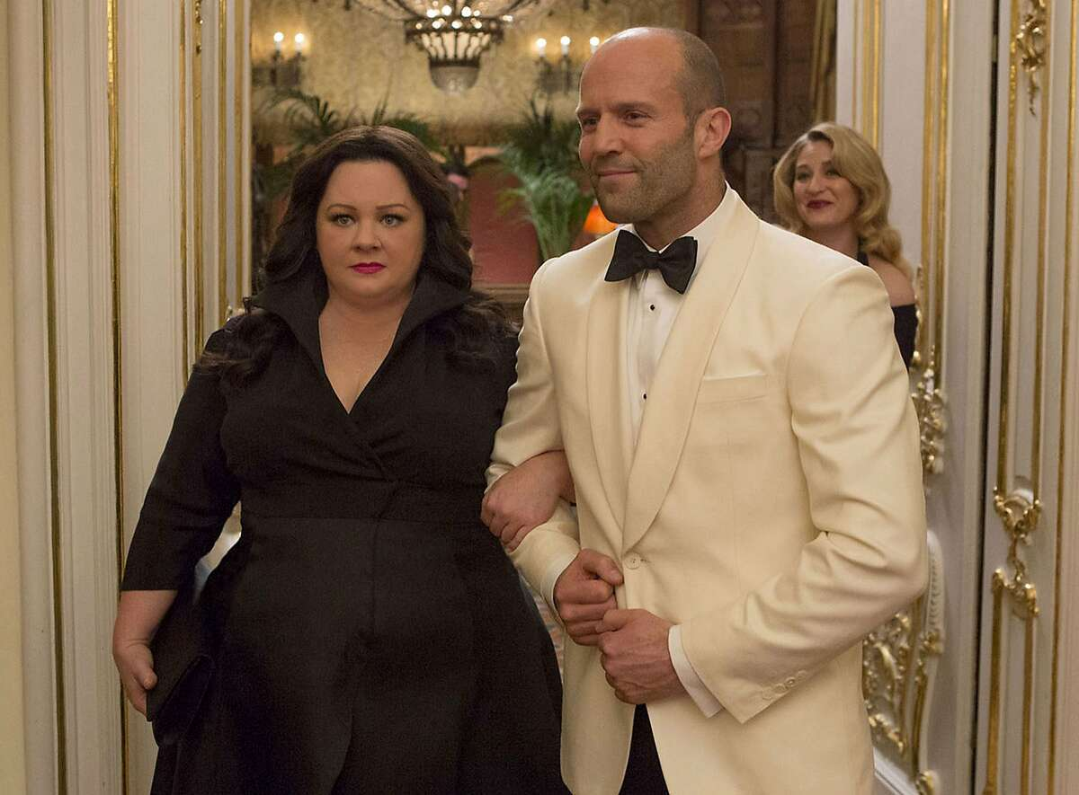 """Susan Cooper (Melissa McCarthy) and her fellow CIA operative Rick Ford (Jason Statham) pose as a """"happy"""" couple as they go deep undercover to stop an arms dealer in """"Spy."""" Illustrates FILM-SPY-ADV05 (category e), by Ann Hornaday © 2015, The Washington Post. Moved Wednesday, June 3, 2015. (MUST CREDIT: Larry Horricks/Twentieth Century Fox.)"""
