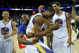 Golden State Warriors' Harrison Barnes is hugged by Festus Ezeli after Barrnes' game-winning shot against Phoenix Suns during Warriors' 107-106 win in NBA game at Oracle Arena in Oakland, Calif., on Thursday, April 2, 2015.