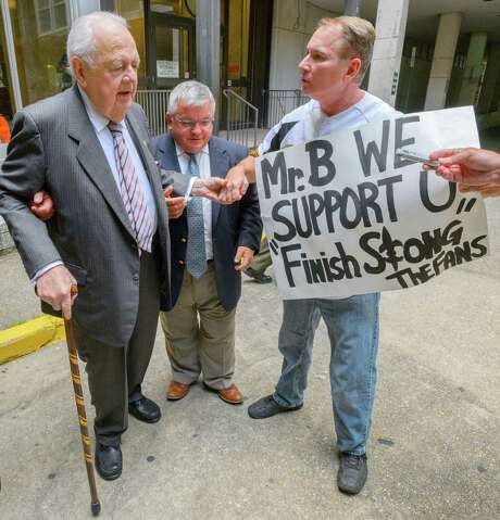 Tom Benson (left), owner of the New Orleans Saints and Pelicans sports teams, is greeted by Larry Rolling, a Saints season ticket holder for 37 years, Wednesday outside Orleans Parish Civil District Court. Photo: Matthew Hinton /The Advocate / The Advocate