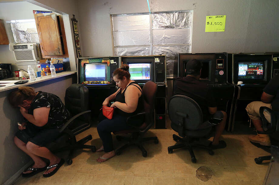 Gamblers wait to be questioned by agents from the Cameron County District Attorney's Special Investigations Unit during a raid of an underground gambling establishment outside of San Benito, Texas, Wednesday, June 3, 2015. The raid is part of Operation Bishop and is aimed that the illegal gambling establishments. Officers found 25 of the eight liner machines known as maquinitas and ticketed nine people for illegal gambling that carries a fine of up to $500. Photo: JERRY LARA, Staff / San Antonio Express-News / © 2015 San Antonio Express-News