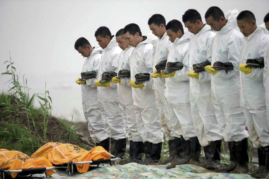 Rescuers observe a moment of silence for victims recovered from the tourist ship Dongfangzhixing, or Eastern Star. Photo: Associated Press / CHINATOPIX