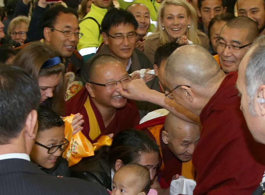 The Dalai Lama, center right, pinches the nose of a well-wisher as he arrives in Sydney, Thursday, June 4, 2015. The Tibetan spiritual leader is visiting Australia for the 10th time. Photo: Rick Rycroft, Associated Press